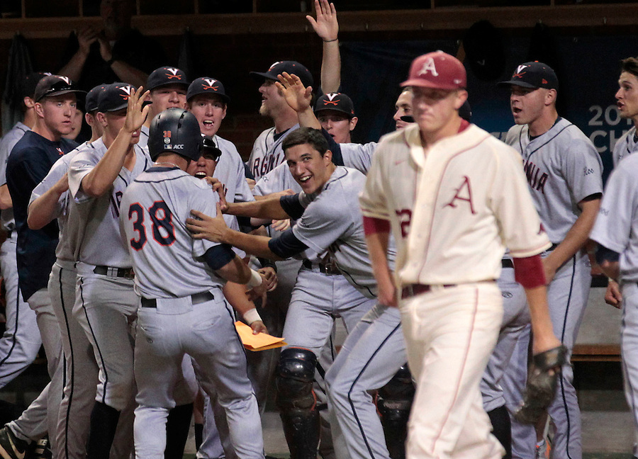 Virginia players celebrate teammate Mike Papi (38) after scoring in front of Arkansas pitcher Zach Jackson (32) during an NCAA college baseball regional tournament game against in Charlottesville, VA., Sunday, June 1, 2014. (Photo/Andrew Shurtleff)