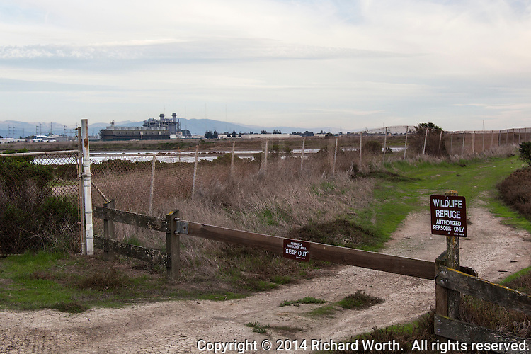 Wildlife Refuge and Keep Out signs in foreground and a natural gas-fired electric power plant behind a fence in the background.