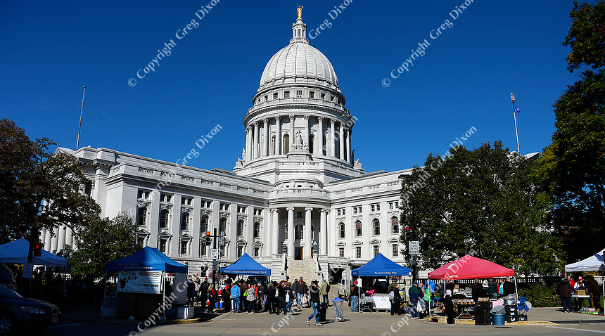 People enjoy the Dane County Farmers' Market as they walk around Capitol Square on Saturday, October 17, 2015 in Madison, Wisconsin