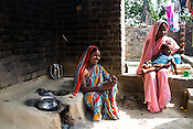 21 year old Seema Devi (right) and her sister-in-law (left) sit in their kitchen of their hut in Shivpur Hariyya village in Raxaul district of Bihar.