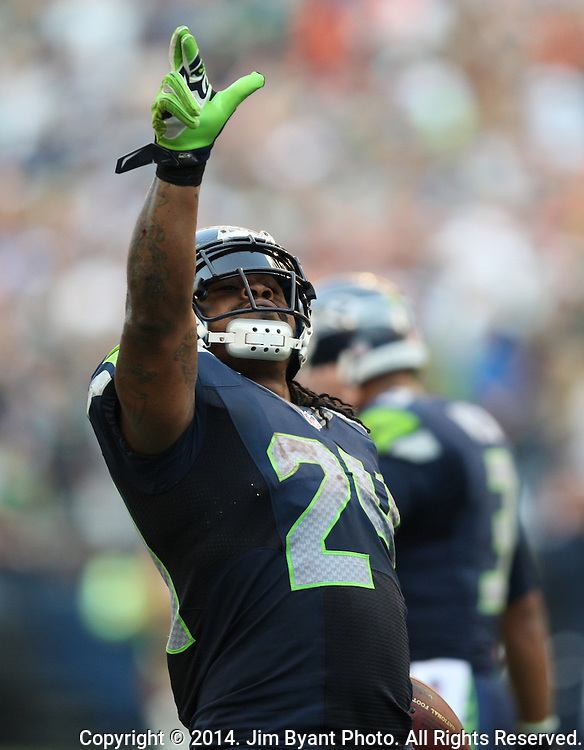 Seattle Seahawks running back Marshawn Lynch points to the crowd after scoring the winning touchdown against the Denver Broncos in overtime at CenturyLink Field in Seattle, Washington on September 21, 2014. The Seahawks won 26-20 in overtime.      ©2014. Jim Bryant Photo. All rights Reserved.