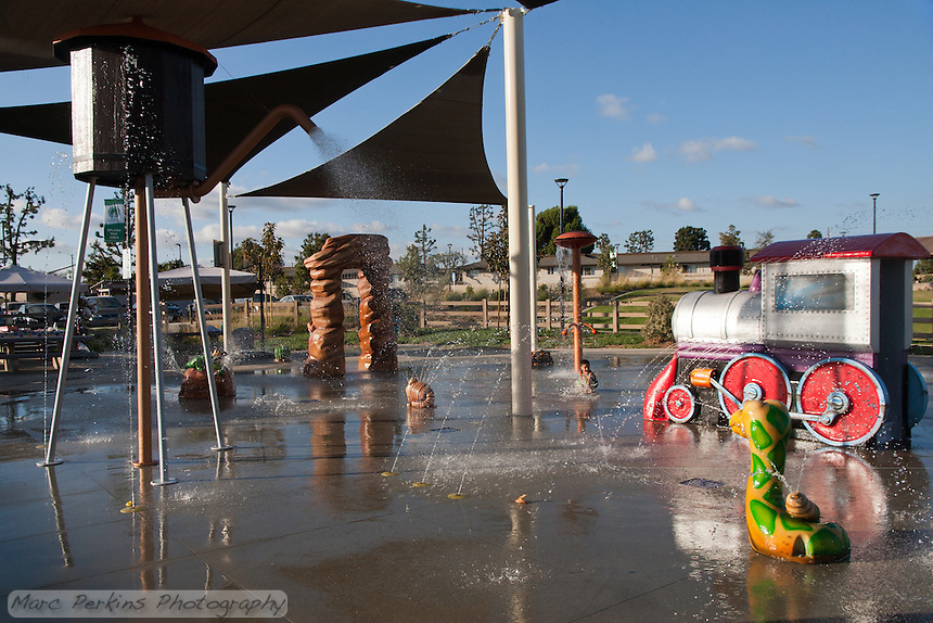 A boy crouches down in front of a water jet at the splash pad at Stanton Central Park.  Two girls are barely visible, hiding behind the arch.  This view shows most of the water features in the splash pad area, including the shade structures, water-spraying water tower, and multiple animals.