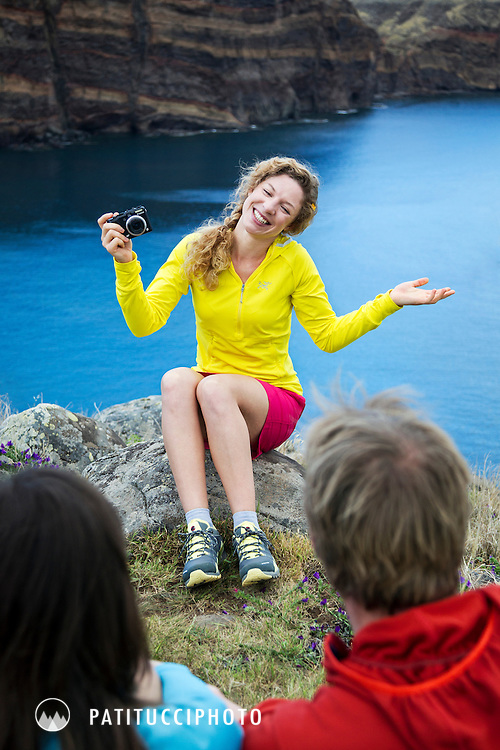 A group of friends hiking on Madeira Island stopped to make photos, sit laughing and joking