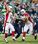 Arizona Cardinals quarterback Drew Stanton (5) passes against the Seattle Seahawks while being pass rushed by defensive end Cliff Avril (56) at CenturyLink Field in Seattle, Washington on November 23, 2014. Stanton completed 14 of 26 passes for 149 yards and had one interception in the Cardinals 3-19 loss to the Seahawks. ©2014. Jim Bryant Photo. All Rights Reserved.
