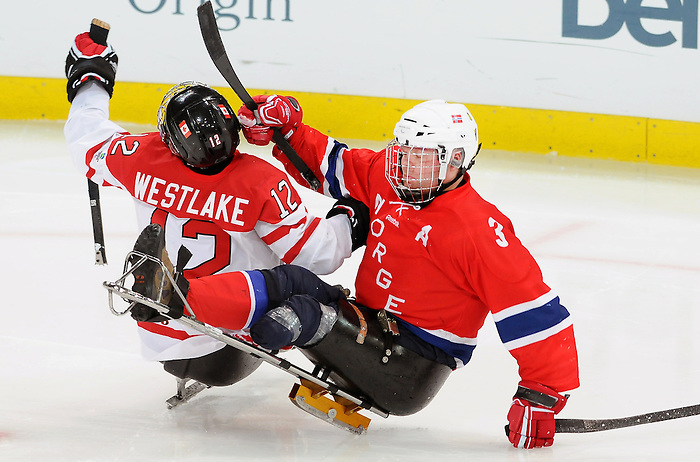 Greg Westlake takes a high hit during 2010 Paralympic Games sledge hockey action at UBC Thunderbird Arena in Vancouver. Credit: CPC/HC/Matthew Manor.