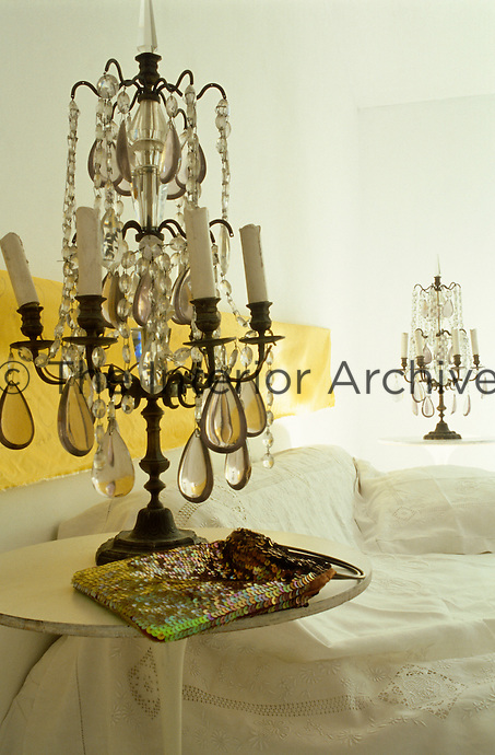 A pair of antique candelabra with crystal drops has been used as bedside lights