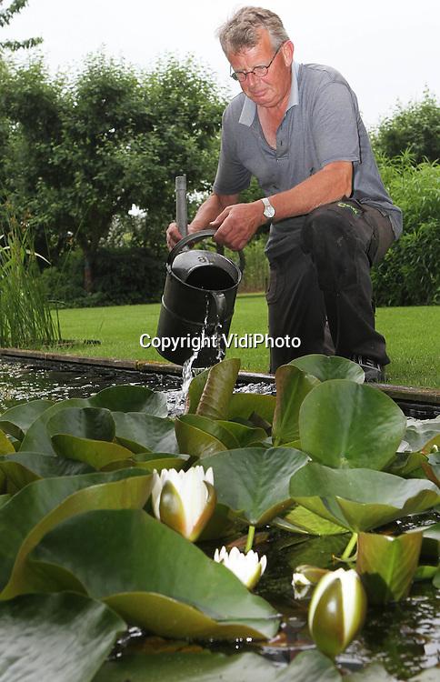 Foto: VidiPhoto..ZETTEN - Joop Galema uit Zetten in de Betuwe perfectioneert donderdag samen met buurvrouw Elly Reems zijn 1500 vierkante meter grote tuin. Op dit moment doen meer dan duizend trotse tuinbezitters hetzelfde. Dit weekend houdt de grootste tuinvereniging van Nederland, Groei & Bloei, zijn jaarlijkse Open Tuinen Weekend, waarbij ruim duizend particulieren hun tuinen open stellen voor publiek. Groei & Bloei heeft 145 afdelingen en 50.000 leden. De 'kijktuinen' zijn te vinden op www.groei.nl.