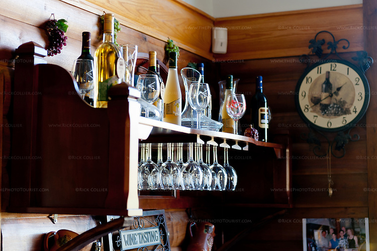 Shadow and light from a nearby window play amongst the bottles and glasses on a shelf behind the bar at Mediterranean Cellars.
