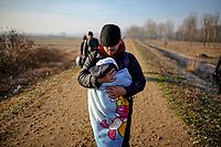 Pictured: A migrant father holds his baby child as he walks by the Turkish side of the border. Sunday 01 March 2020<br /> Re: Clashes between migrants and riot police at the Greek-Turkish border of Kastanies near Evros, Greece