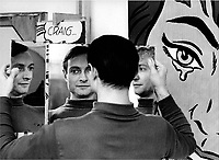 Roy Lichtenstein holding a mirror to get a better view of his work.