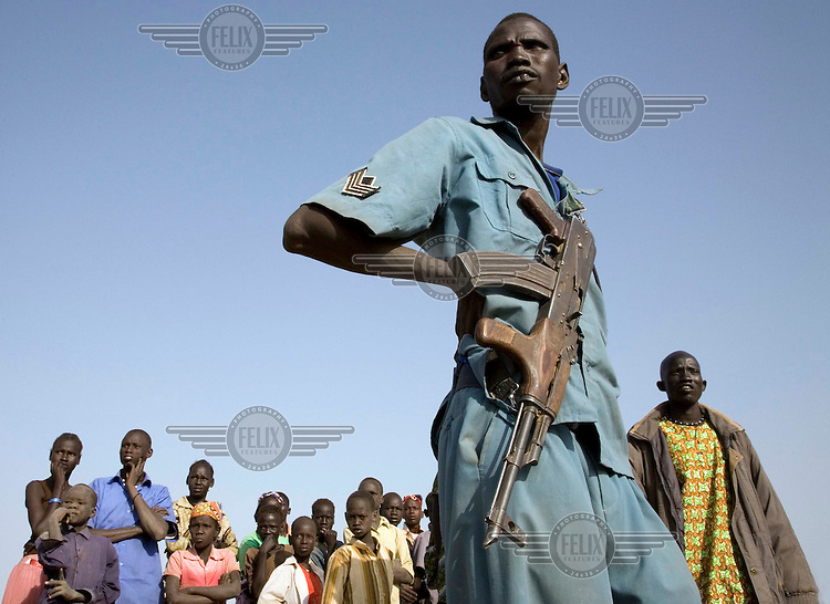 An SPLM/SPLA (Sudan Peoples' Liberation Movement) Policeman watches a football match with other spectators at the Twic Olympics in Wunrok, Southern Sudan.