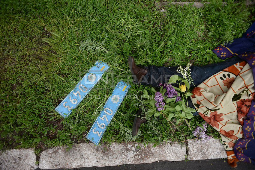 The corpse of a civilian shot dead lies in the street nearby the Mariupol police headquarters. Plates of defeated vehicles are placed on the side the victims of the battle.<br />