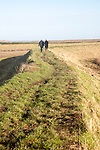 Two people walking on coastal defence wall at Shingle Street, Suffolk, England