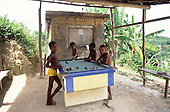 Itaparica Island, Brazil. Four boys of mixed race playing pool in a shelter without walls in a rural location. Bahia State.