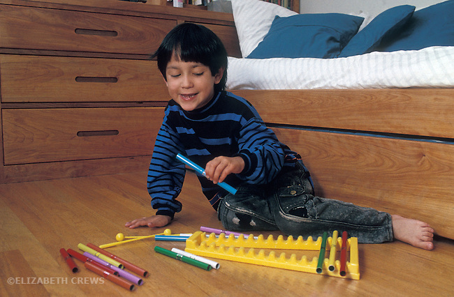 Berkeley CA Boy, (half-Latino) four-years-old doing seriation with xylophone tubes  MR
