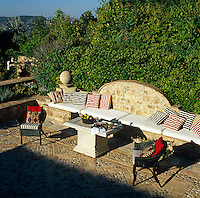 Shadows creep over a stone terrace with cushions and mattresses spread along a built-in stone banquette