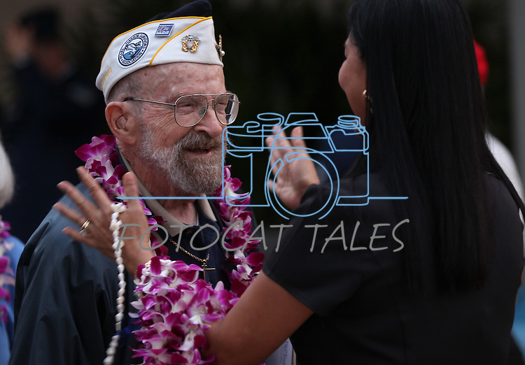 Naty Delapena, with the Navy Federal Credit Union, gives a lei to Pearl Harbor survivor Edward Vezey, Jr., 92, before the 71st Anniversary Pearl Harbor Day Commemoration at the Pearl Harbor Visitor Center in Honolulu, HI on, Dec. 7, 2012. .Photo by Cathleen Allison