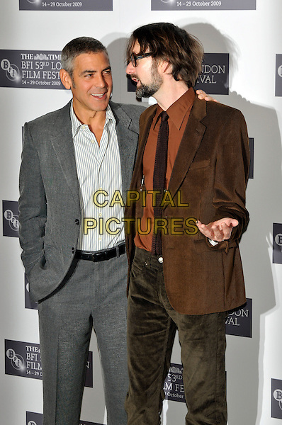 GEORGE CLOONEY & JARVIS COCKER .The 'Fantastic Mr. Fox' photocall during the Times BFI 53rd London Film Festival,  Dorchester Hotel, London, England..October 14th, 2009 .half 3/4 length shirt grey gray suit striped stripes shirt white blue hand in pocket brown glasses hand beard facial hair profile .CAP/PL.©Phil Loftus/Capital Pictures.