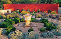 Gardenerand artist Sally Shoemaker created a red wall and scripted it with with an inspiring quotation from George Bernard Shaw to compliment the fountain and  drought tolerant plantings in her Phoenix garden