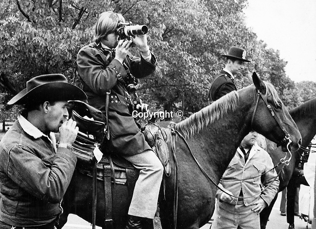 Photojournalist Ron Bennett shooting pictures from a horse, Photojournalism, Photojournalist, News, sports, features, Hollywood, White House, &quot;Photography is art at the speed of light,&quot;<br /> Political,  &quot;Photography is art at the speed of light,&quot;<br /> collecting, editing, presenting news photographs, Photojournalism provides visual support for stories mainly in the print media,  Commercial photography's main focus is to sell a product or service, Fine Art photography are photographs that are created to fulfill the creative vision of the photographer,