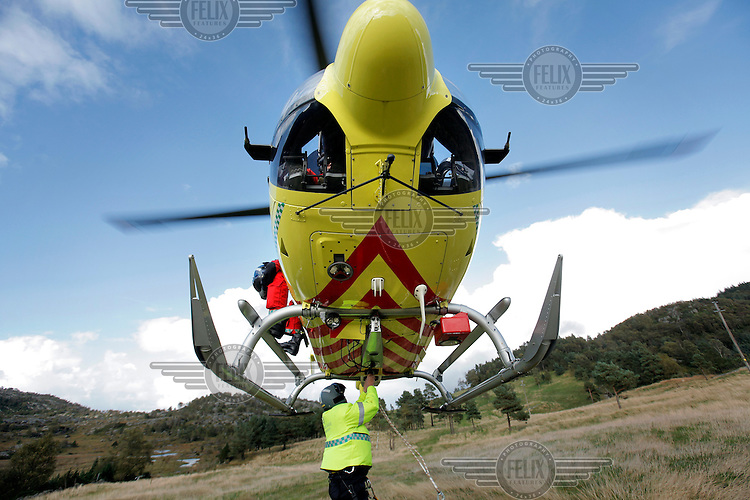 Norwegian Air Ambulance crew in EC-135 helicopter on rescue training mission near Stavanger. Rescue professional Jørn Holmestrand attaches a long line under the helicopter.