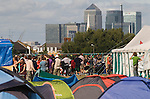 Climate Camp Blackheath south London UK. Canary Wharf docklands in background. Campers in food queue.  2009