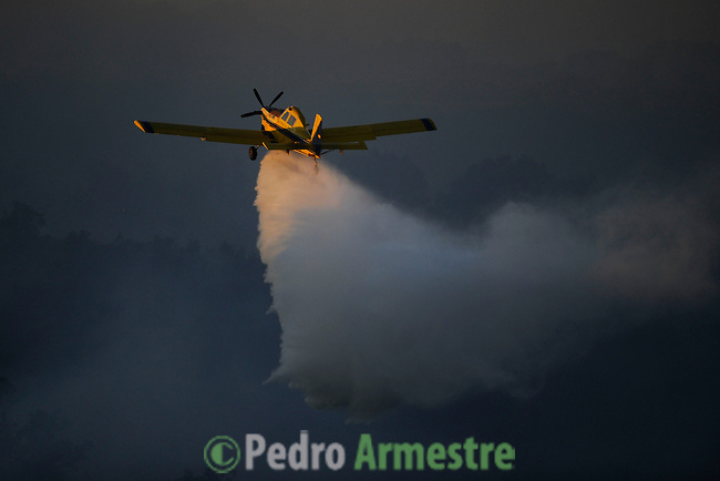 A plane drops water during a wildfire in Seoane de Oleiros near Ourense on August 25, 2013. (c) Pedro ARMESTRE