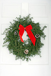 A Christmas wreath hanging on the white front door of a home