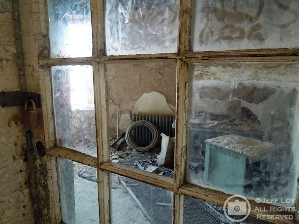 Looking into an abandoned office through a broken windown pane at Eastern State Penitentiary in Philadelphia, Pennsylvania. The site is considered to be the world's first true penitentiary and when it opened in 1829, inmates were kept in complete solitary confinement. The penitentiary was closed in 1971 and is now a historical site and tourist attraction.