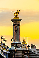 Pont Alexandre III (bridge) across the Seine River with Hotel des Invalides in background. The bridge is the most ornate in the city and features art nouveau lamps, cherubs, nymphs and on the two large gilded sculptures at the end, winged horses. Paris, France.