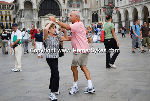 Venice Italy 2009. Couple of tourists dancing in St Marks Square. Piazza Sab Marco. Basilica San Marco in background.