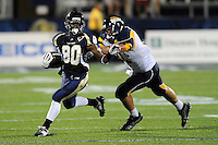 26 September 2009:  FIU wide receiver Jason Frierson (80) attempts to evade Toledo tight end Tom Burzine (81) while returning a punt in the first quarter of the Toledo 41-31 victory over FIU at FIU Stadium in Miami, Florida.