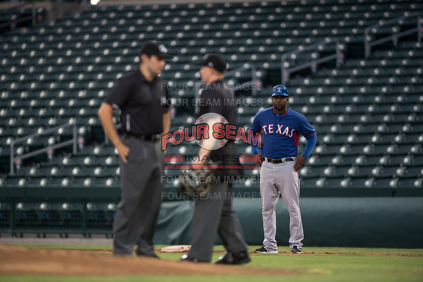 AZL Rangers first base coach Jeremy Moore (43) watches as umpires Alan Gorewitz and Austin Nelson discuss the ruling of a play during an Arizona League game against the AZL Cubs 2 at Sloan Park on July 7, 2018 in Mesa, Arizona. AZL Rangers defeated AZL Cubs 2 11-2. (Zachary Lucy/Four Seam Images)
