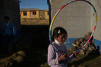 Nelsi Nieto Aguirre plays with a hoola hoop near her home in Villa Pasco, 15 km from the city of Cerro de Pasco, Peru. Villa Pasco was designated as a potential site to relocate the population of the contaminated mining city of Cerro de Pasco. Electricity, water and homes were build in the 1990's, but today 70% of the homes are empty. Residents of Cerro de Pasco complained that the homes are too small to live in. This family is one of the few that relocated, and the father currently commutes to work in the mine.