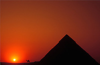 Egypt. Cairo.  The Pyramids at Giza at sunset, with camel silhouette
