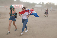 Revellers fight a sand storm caused by high wind before storm arrives to Sziget Festival held in Budapest, Hungary on Aug. 14, 2018. ATTILA VOLGYI