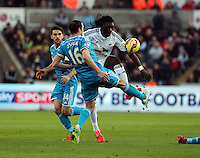SWANSEA, WALES - FEBRUARY 07: Bafetimbi Gomis of Swansea (R) is fouled by John O'Shea of Sunderland (C) during the Premier League match between Swansea City and Sunderland AFC at Liberty Stadium on February 7, 2015 in Swansea, Wales.