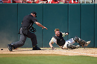 Home plate umpire Mike Jarboe makes a safe signal as Army Black Knights catcher Jon Rosoff (7) loses his glove on a play at the plate against the North Carolina State Wolfpack at Doak Field at Dail Park on June 3, 2018 in Raleigh, North Carolina. The Wolfpack defeated the Black Knights 11-1. (Brian Westerholt/Four Seam Images)