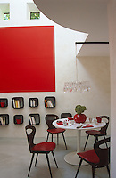 A  Saarinen tulip table occupies a corner of this red and white living space