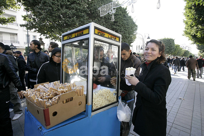 Tunisians Selling popcorn during protest for Tunisians amongst them policemen, gather to ask for the right to form unions and better salaries as the vehicle of Tunisian interim President Fouad Mbazaa (not in picture) arrives at the government Palace in Tunis, Tunisia, 22 January 2011. Tunisians began a three-day national mourning period on 21 January in memory of the victims of the latest events which led to the departure of former President Zine el-Abedine Ben Ali and the formation of an interim government. Photo by Karam Nasser
