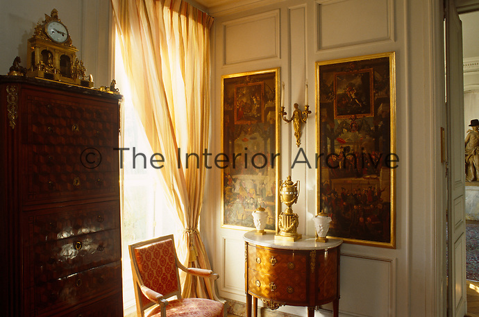 A pair of Renaissance paintings hangs on the panelled wall of the bedroom