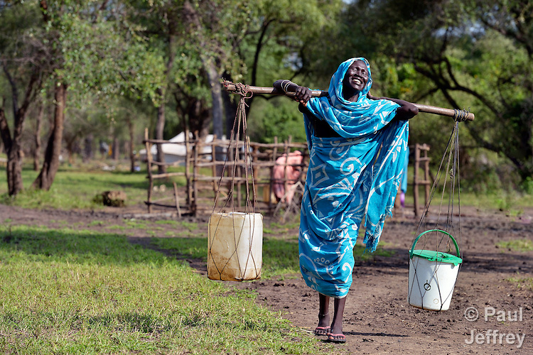 A woman laughs as she carries water through the Gendrassa refugee camp in South Sudan's Upper Nile State. More than 110,000 refugees were living in four camps in Maban County in October 2012, but officials expected more would arrive once the rainy season ended and people could cross rivers that block the routes from Sudan's Blue Nile area, where Sudanese military has been bombing civilian populations as part of its response to a local insurgency. Conditions in the camps are often grim, with outbreaks of diseases such as Hepatitis E.