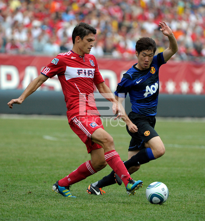 Chicago Fire defender Josip Mikulic (23) passes the ball away from Manchester United midfielder Ji-Sung Park (13).  Manchester United defeated the Chicago Fire 3-1 at Soldier Field in Chicago, IL on July 23, 2011.