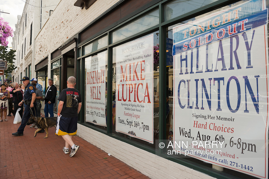 Huntington, New York, U.S. - August 6, 2014 - A police officer and police dog are leaving the Book Revue, a few hours before a book signing for H. Clinton's new memoir, Hard Choices, starts at the Book Revue in Huntington, Long Island. A large sign on the book store window says that the Clinton book signing that night is Sold Out.