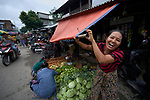 A woman extends an awning as it starts to rain in the Tahan Market in Kalay, a town in Myanmar. This market is located in Tahan, the largely ethnic Chin section of the town.