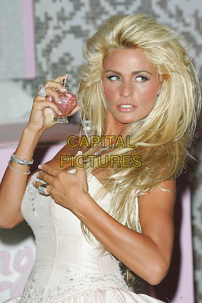 "KATIE PRICE .Fragrance launch & photocall for her new perfume ""Stunning"" at The Roof Gardens, Kensington High Street, London, England, August 20th, 2007. .jordan half length holding bottle ring strapless white pink dress hand.CAP/ROS.©Steve Ross/Capital Pictures"