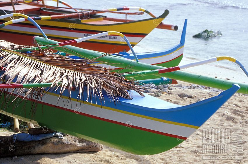 Brightly painted local outrigger canoes on white sand beach, Philippines