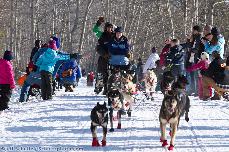 Ramey Smyth and team run past spectators on the bike/ski trail during the Anchorage ceremonial start during the 2013 Iditarod race.    Photo by Britt Coon/IditarodPhotos.com