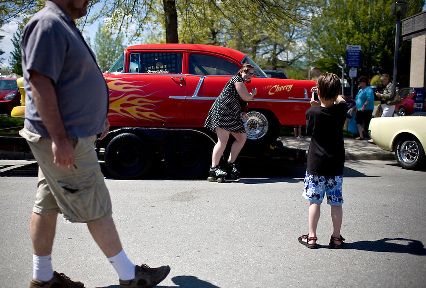 "A woman skating along Second Avenue in Sandpoint, ID stops to have her photograph taken in front of Greg Lassen's hot rod, ""The Cherry"" while another man walks past on Saturday, May 15. People were allowed to wander throughout six square blocks of the downtown area and enjoy the retro cars and trucks. .. (©Matt Mills McKnight/2010)"
