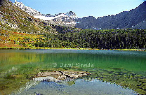 Upper Dewey Lake near Skagway, Alaska reflects the surrounding mountains, trees, and sky.